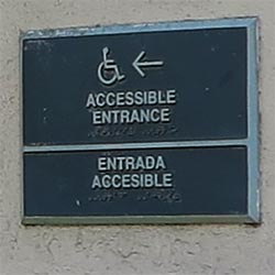 Sign indicates direction to accessible entrance at Olvera Street in downtown Los Angeles. [Photo Credit: LAtourist.com]
