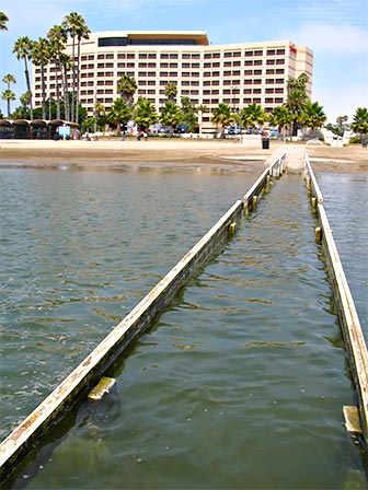 Wheelchair Railing at Mother's Beach in Marina del Rey. The wooden railing is seen here at high tide. The Marriott hotel is in the background. [Photo Credit: LAtourist.com]