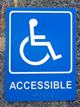 Accessibility Sign with Wheelchair, Accessible and Braille. [Photo Credit: LAtourist.com]