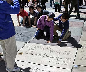 Tourists compare hand prints with a celebrity in the courtyard of the Chinese Theatre Courtyard on Hollywood Boulevard. [Photo Credit: LAtourist.com]