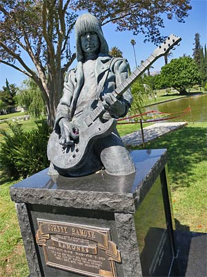 Johnny Ramone's Marker at Hollywood Forever Cemetery. The Hollywood Sign is faintly visible under the neck of the guitar. You can leave guitar picks in Johnny's hand. [Photo Credit: LAtourist.com]