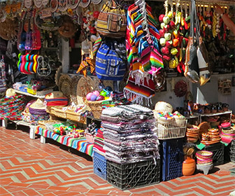 Shop on Olvera Street in Downtown L.A. with blankets, pottery, clothes and other Los Angeles souvenirs. [Photo Credit: LAtourist.com]